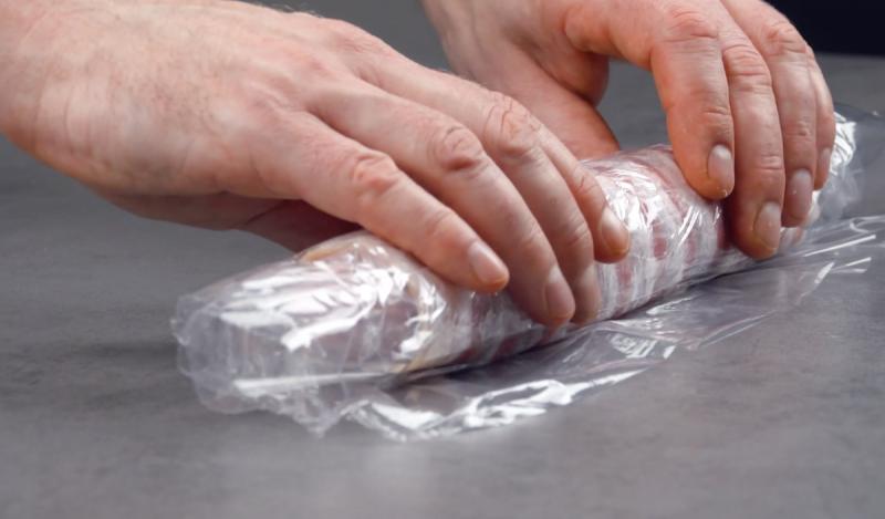 Enrole a linguiça com queijo e bacon no filme plástico