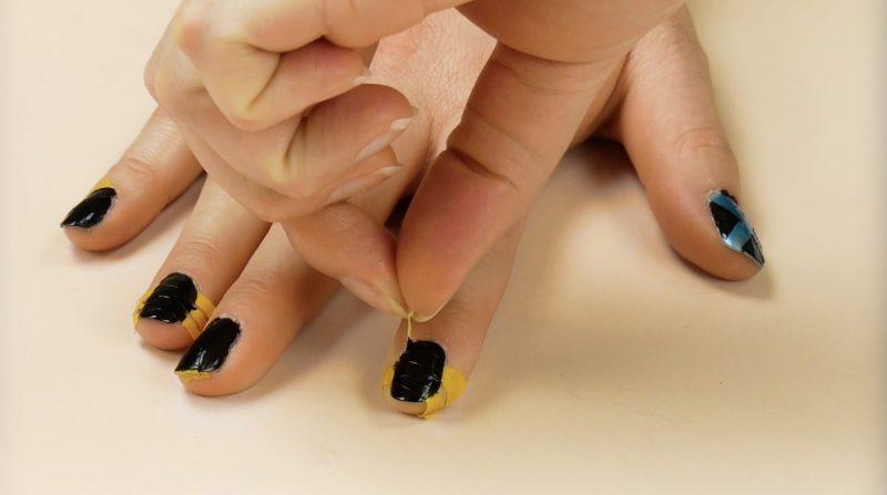 Esmalte preto e tiras de fita adesiva
