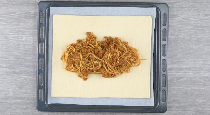 Assadeira forrada com papel manteiga e coberta com massa de pizza e espaguete