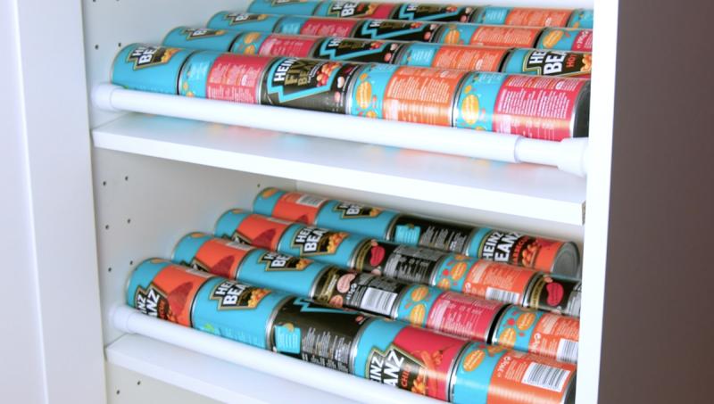 Hastes ajustáveis e prateleira inclinada para organizar latas no armário