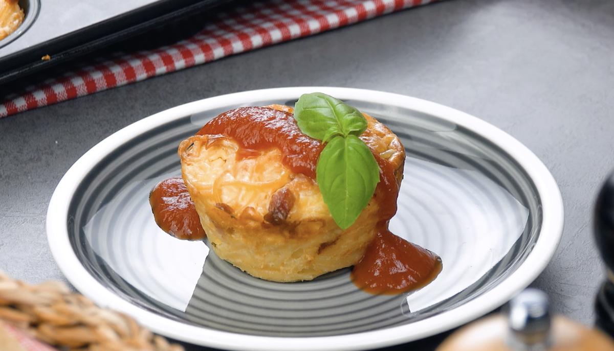 Muffin de espaguete coberto com molho de tomate e uma folha de manjericão