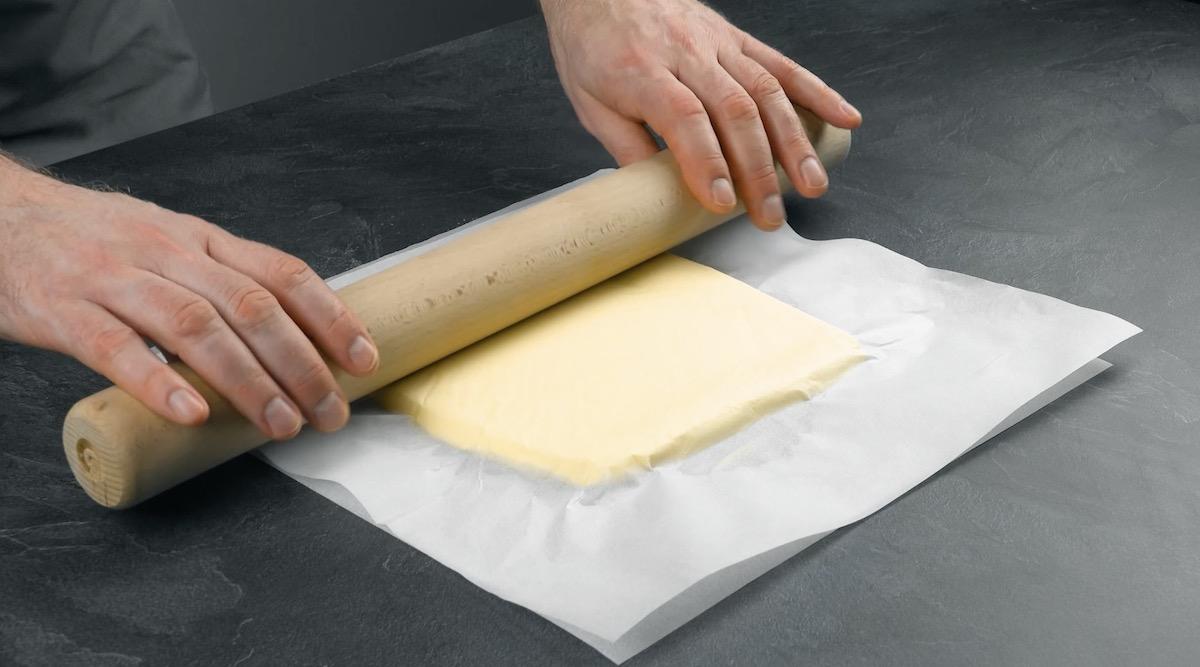 Tablete de manteiga entre folhas de papel manteiga aplainado com rolo