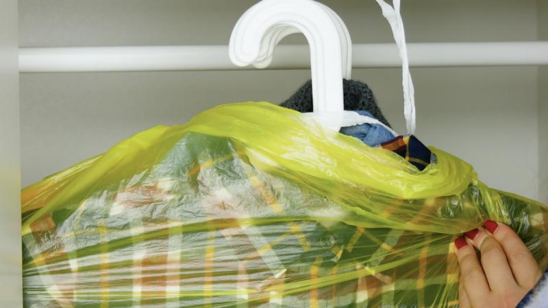 Roupas com cabides embaladas em saco de lixo