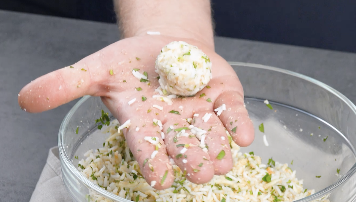Mão segurando bolinha de arroz recheada com mussarela