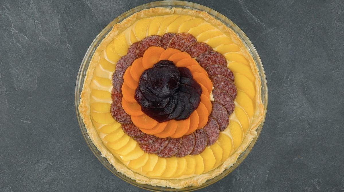 Rodelas de batata, beterraba, salame e cenoura sobre a massa com queijo