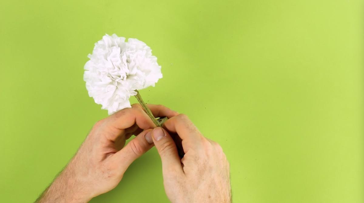 Flor de papel higiênico enrolada em graveto e presa com fita adesiva