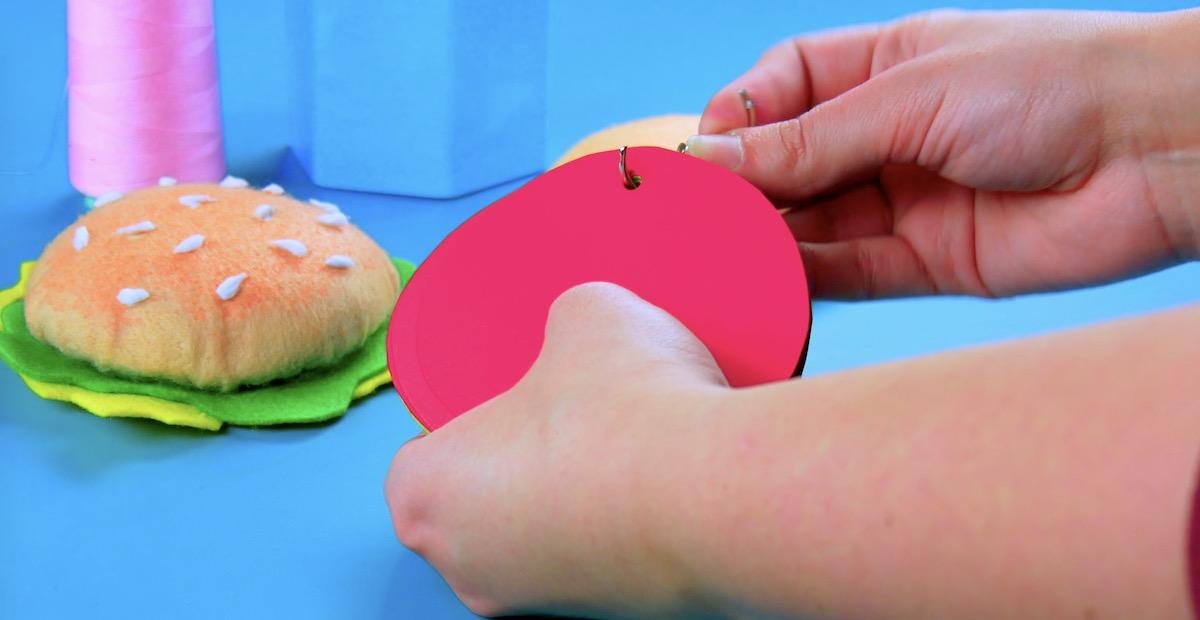Círculos de papel colorido com furo e presos em anel de fichário