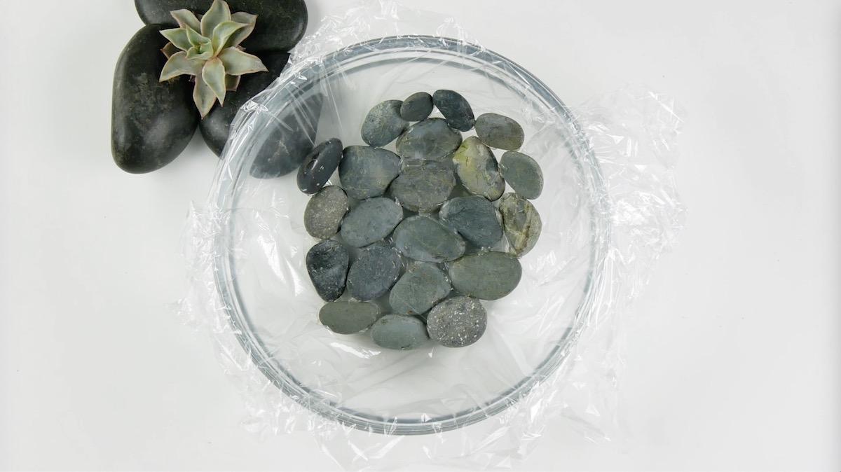 Forre uma tigela com filme plástico e pedras