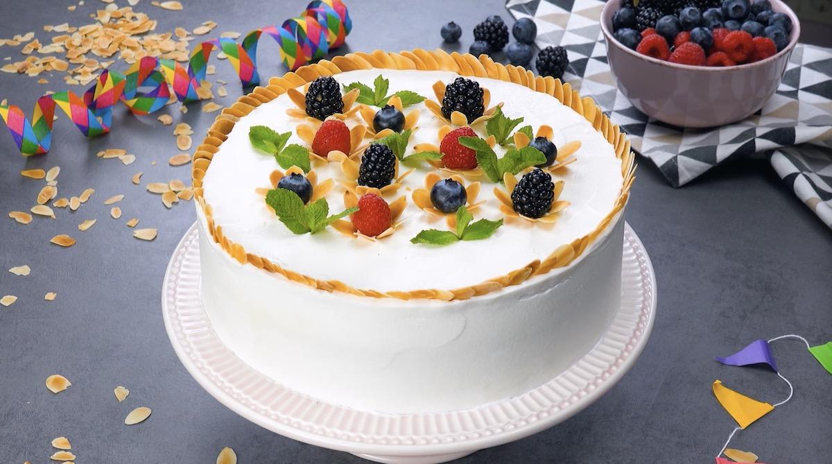 Bolo branco com decoração com flores de frutas e amêndoa