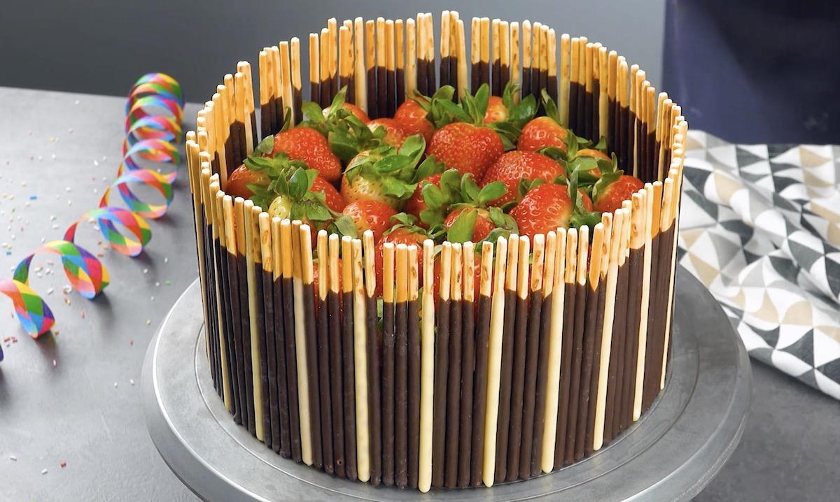 Bolo decorado com palitos de chocolate e morango