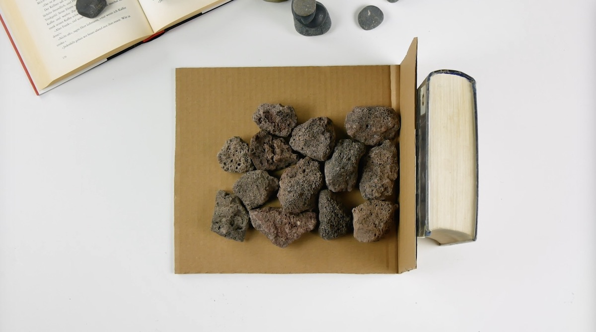 Suporte de livros feito de papelão e pedras