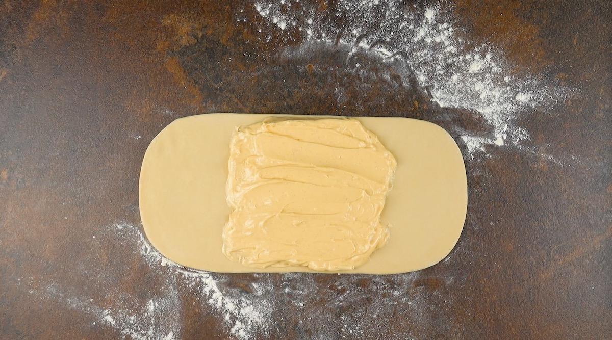 Distribua o pudim de baunilha no centro da massa de pão