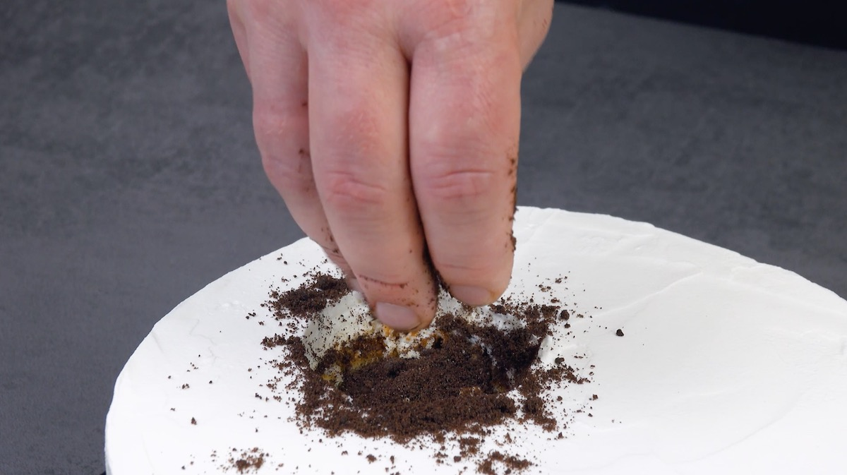 Esfarele o biscoito no buraco do bolo