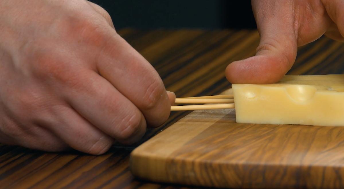 espete os pedaços de queijo com palitos de madeira