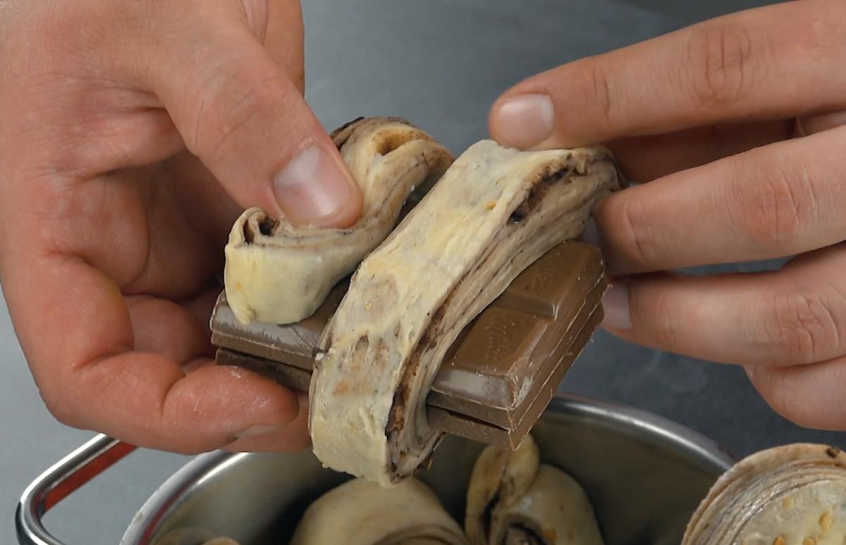 Chocolate enrolado por tira de massa