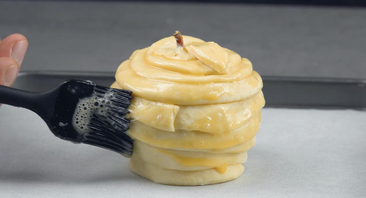 Cubra a maçã com a massa e pincele com ovo