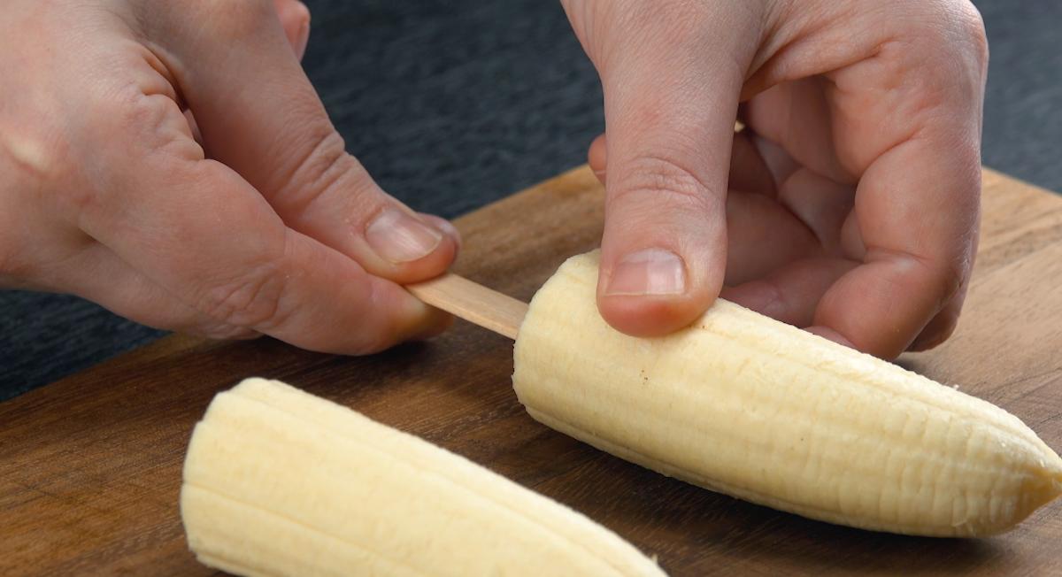 Espete palitos de picolé nas metades de banana