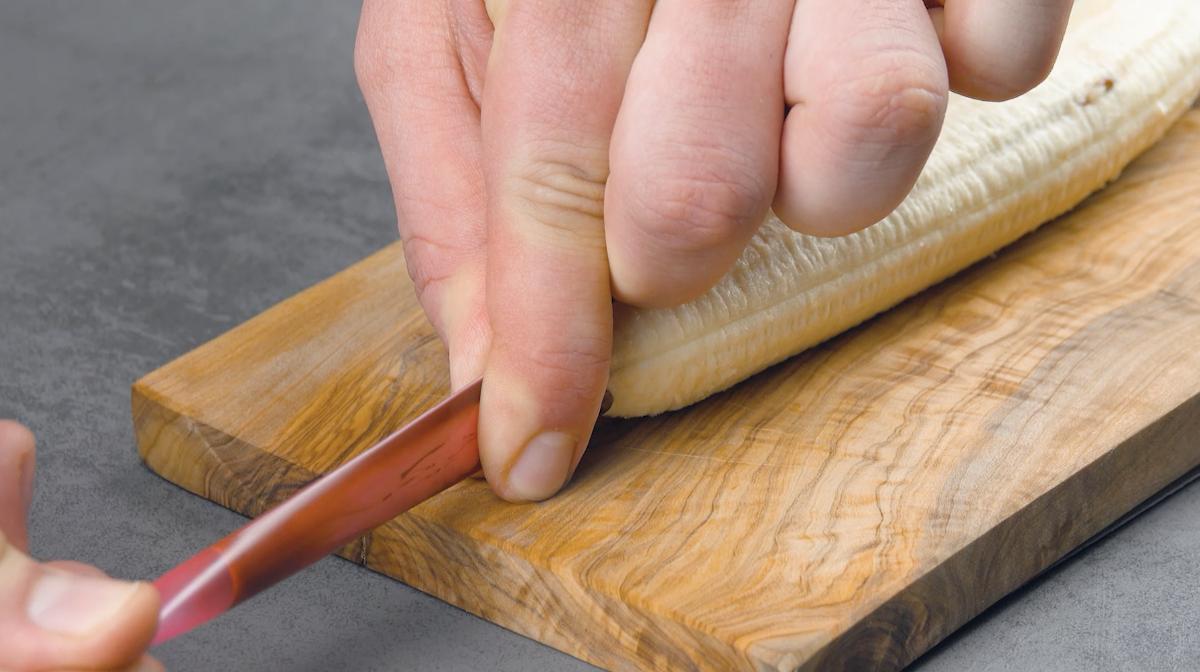 Pressione o canudo cheio de chocolate para rechear a banana