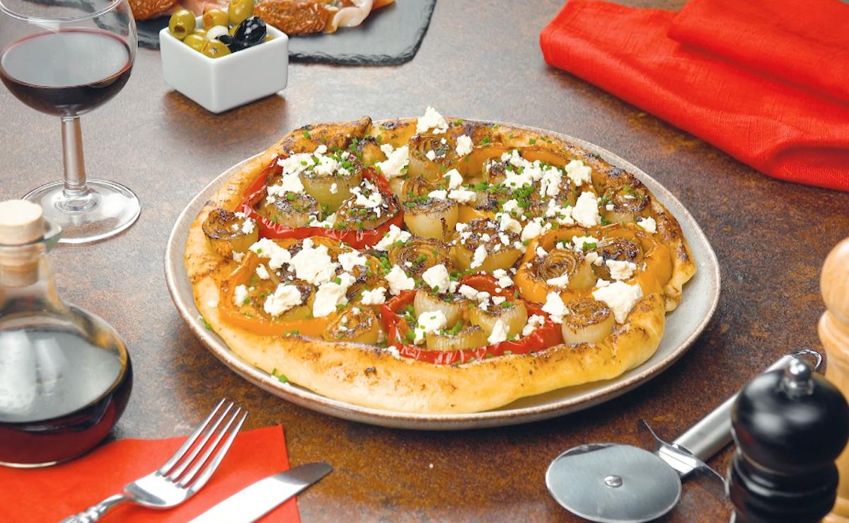 pizza saída do forno, decorada com queijo feta e cebolinha