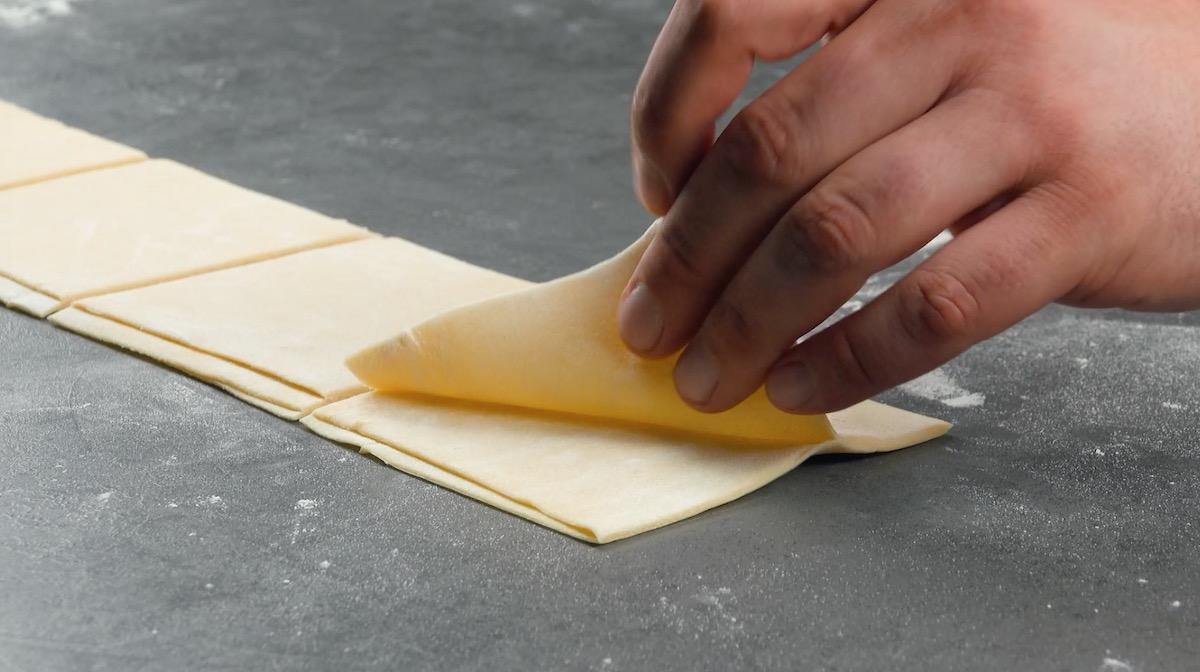 Abra a massa e corte em quadrados finos
