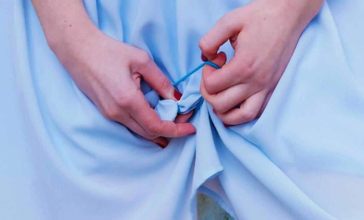 Prenda o vestido com um elástico e uma moeda