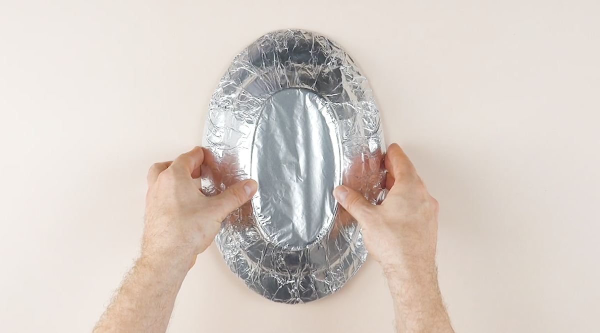 forre um prato oval com papel alumínio