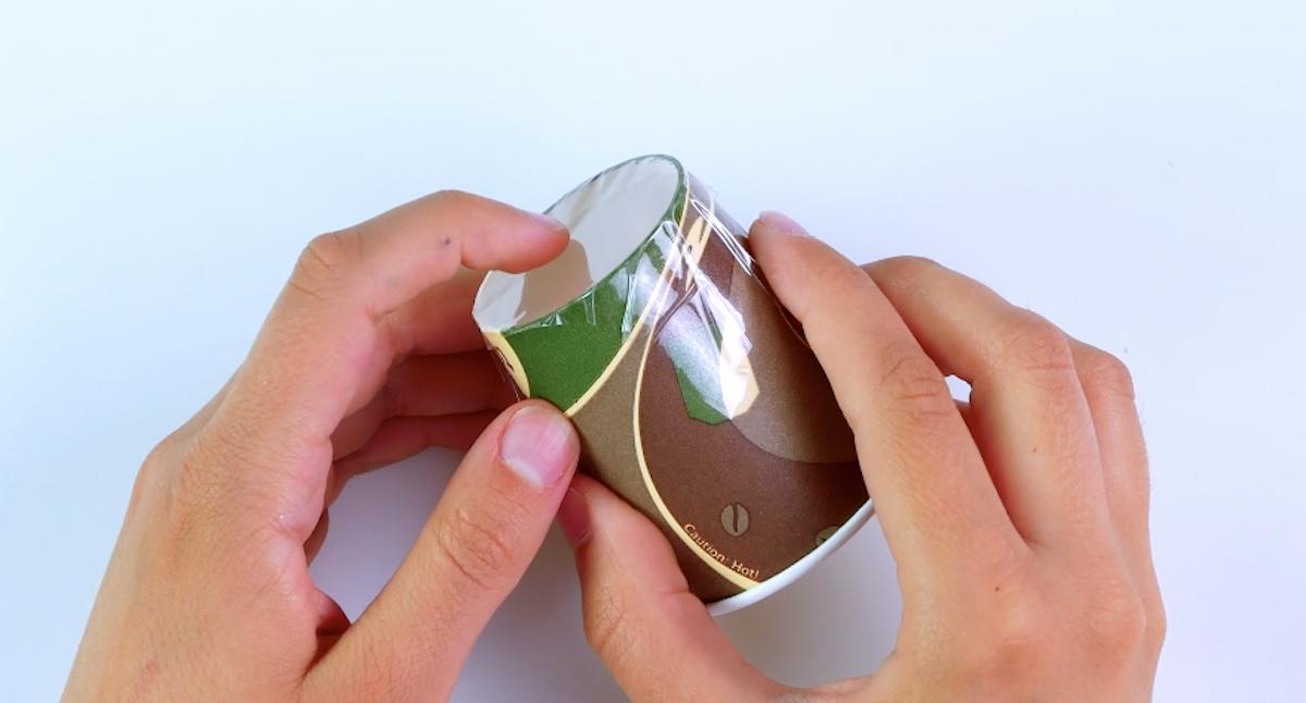 cubra o fundo do copo com um pedaço de fita adesiva