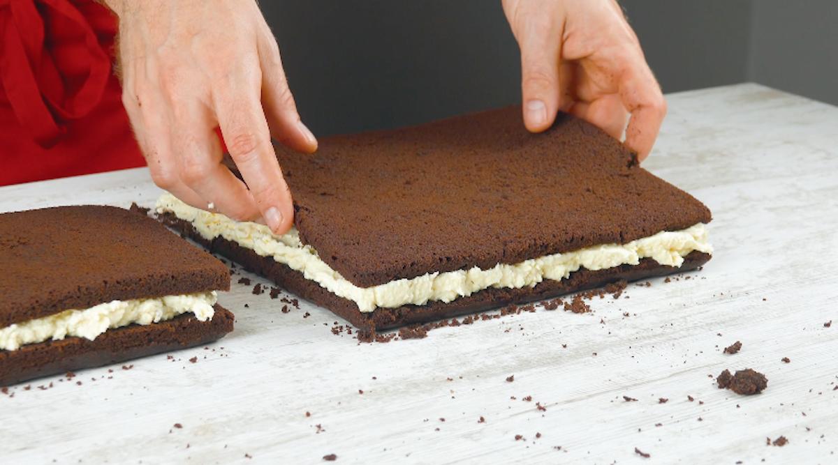 espalhe creme em uma camada de bolo e cubra com outra camada