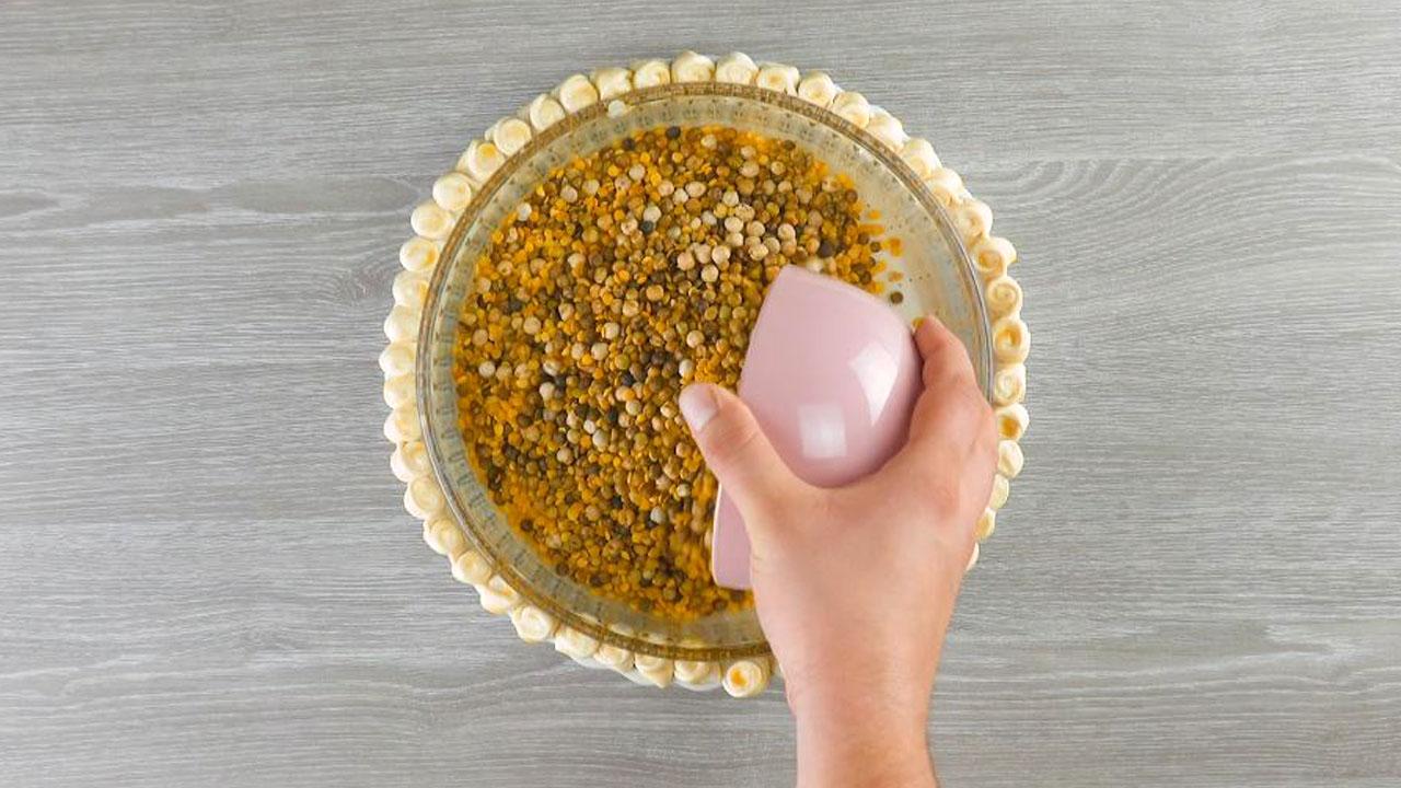 coloque uma forma com leguminosas no meio da massa