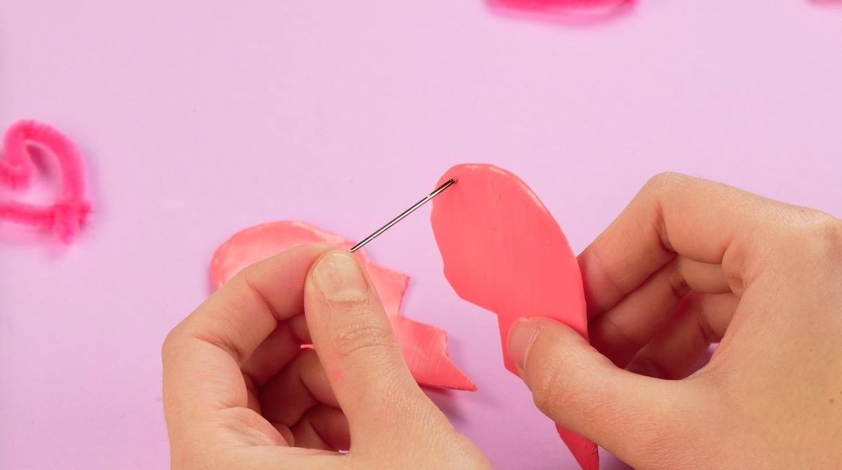 fure as metades do coração com uma agulha