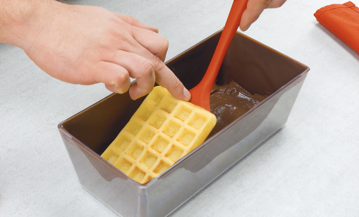comece a montar o bolo com os waffles e creme de chocolate
