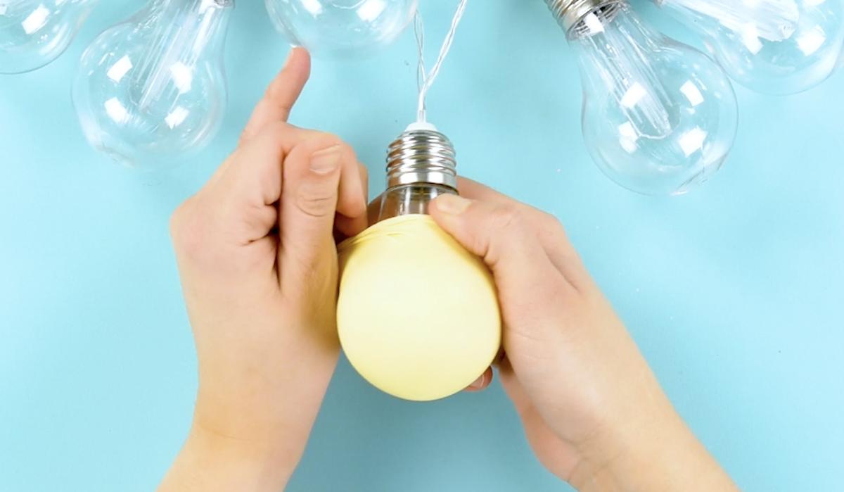 cubra as lâmpadas com os balões coloridos
