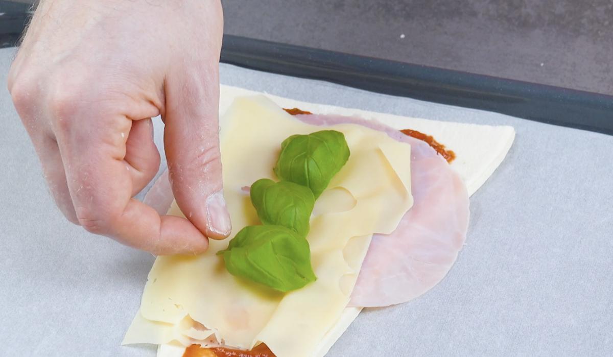 massa de pizza com molho de tomate, presunto, queijo e manjericão