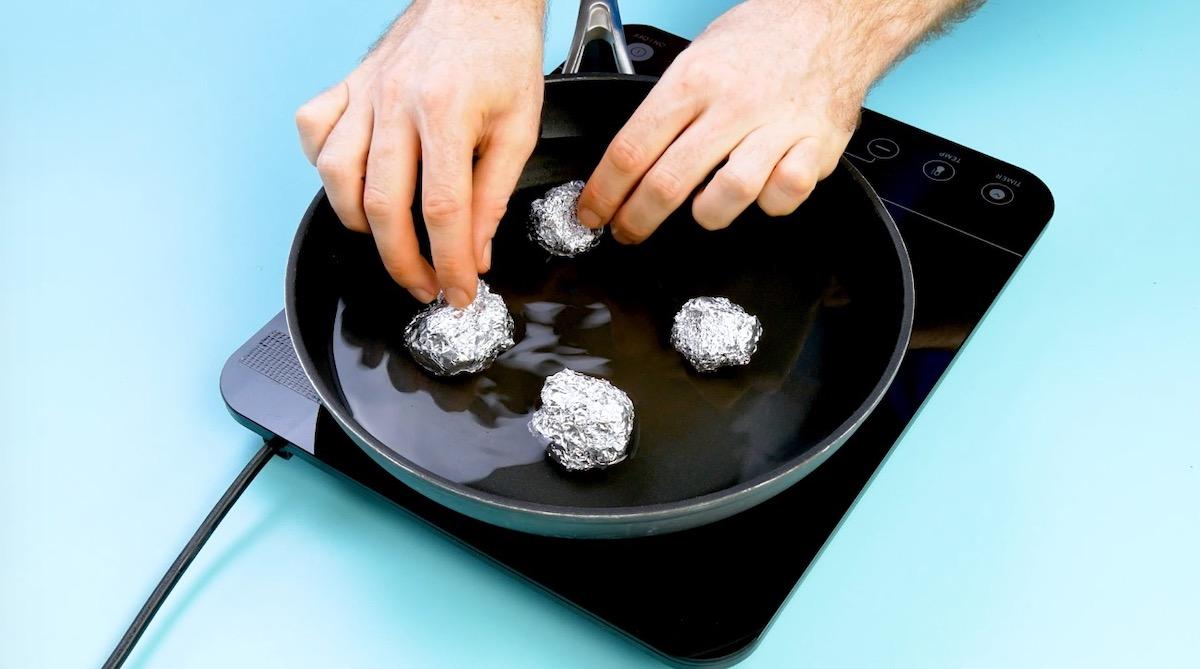 bolas de papel alumínio em panela com água