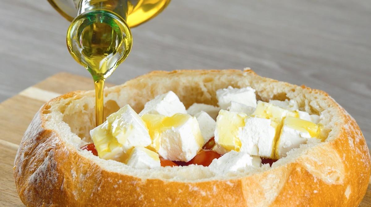 coloque feta e tomate no pão, tempere e regue com azeite