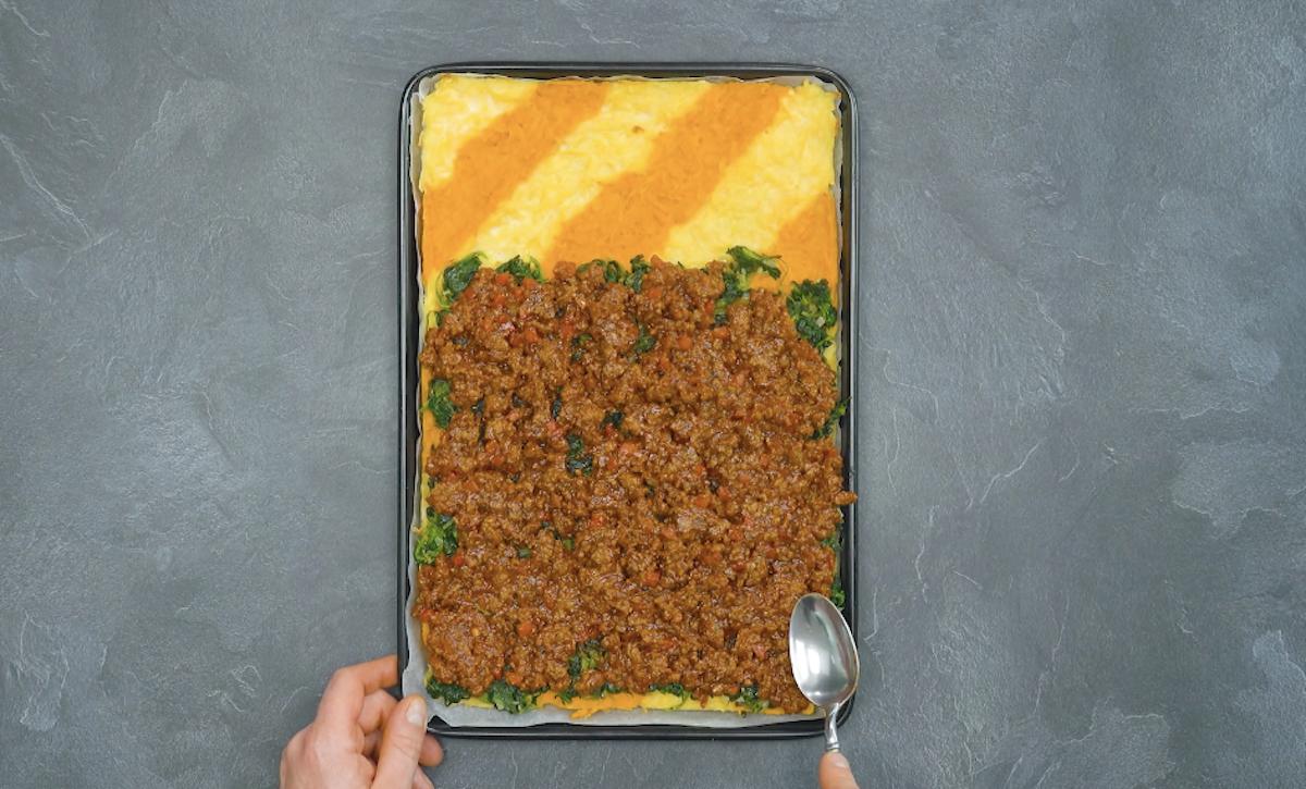 cubra parte das batatas com espinafre e carne moída