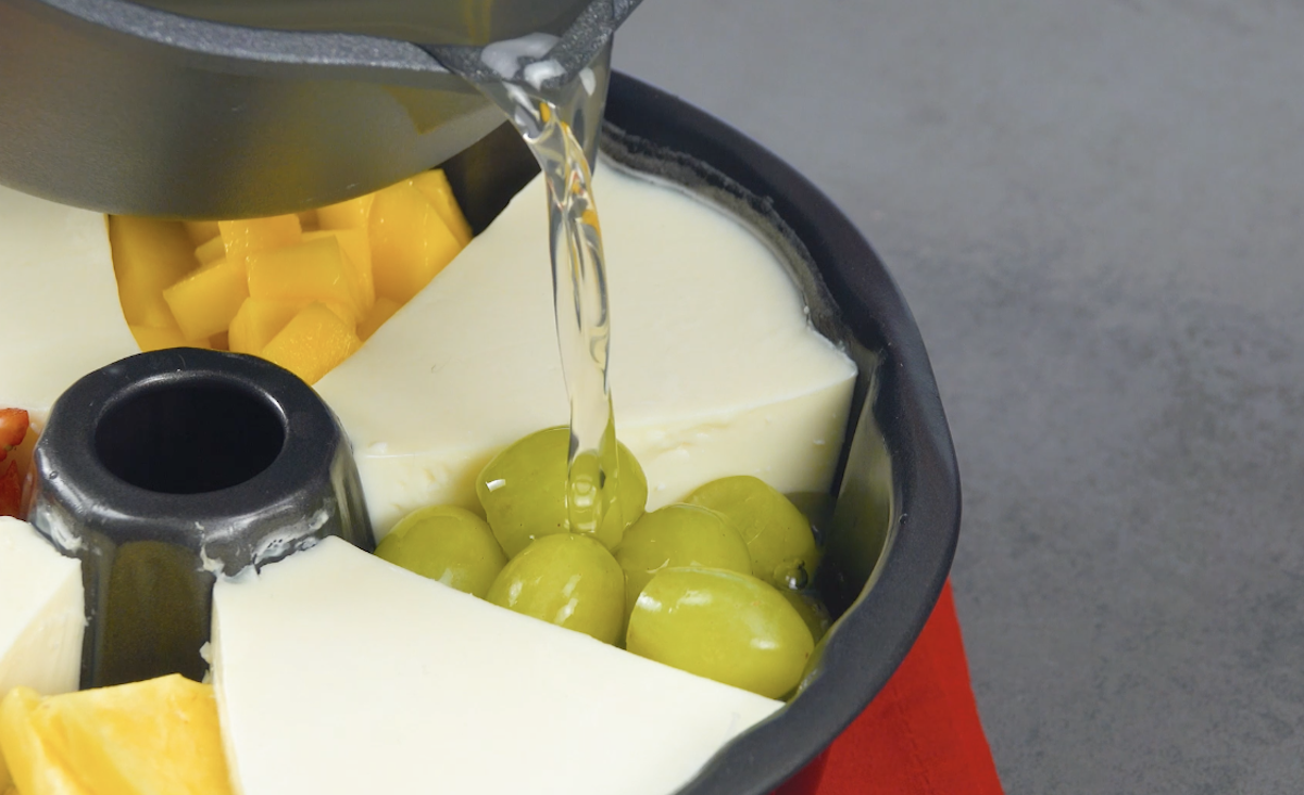 Despeje a gelatina transparente sobre as frutas