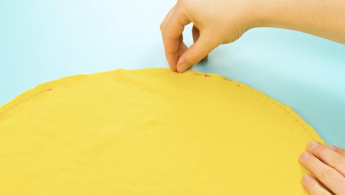 prenda os dois círculos de tecido com alfinetes