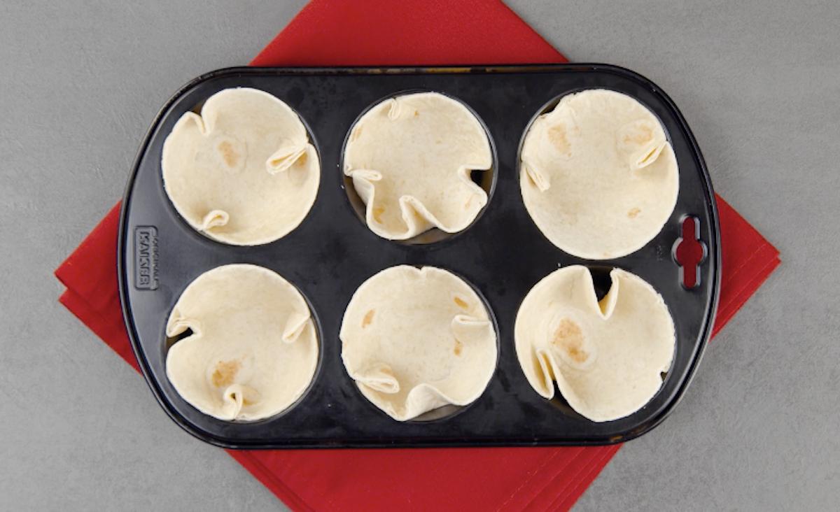 Corte 6 círculos das tortillas e coloque-os em uma forma de muffin