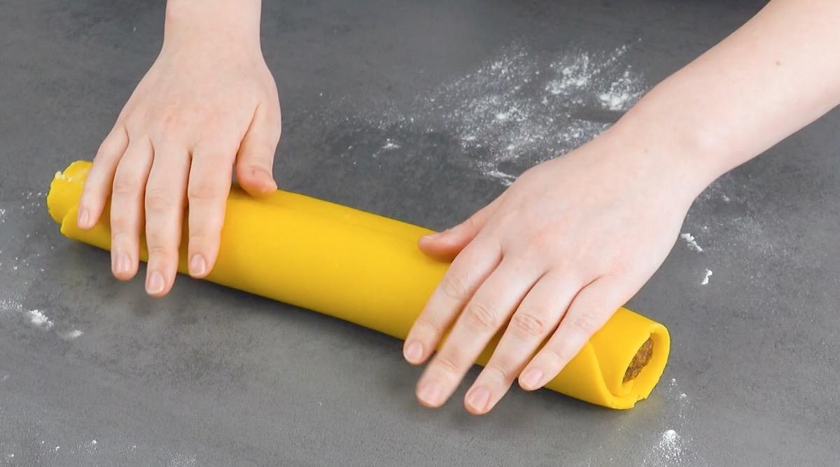 faça um rolo com a massa e a mistura de amêndoas