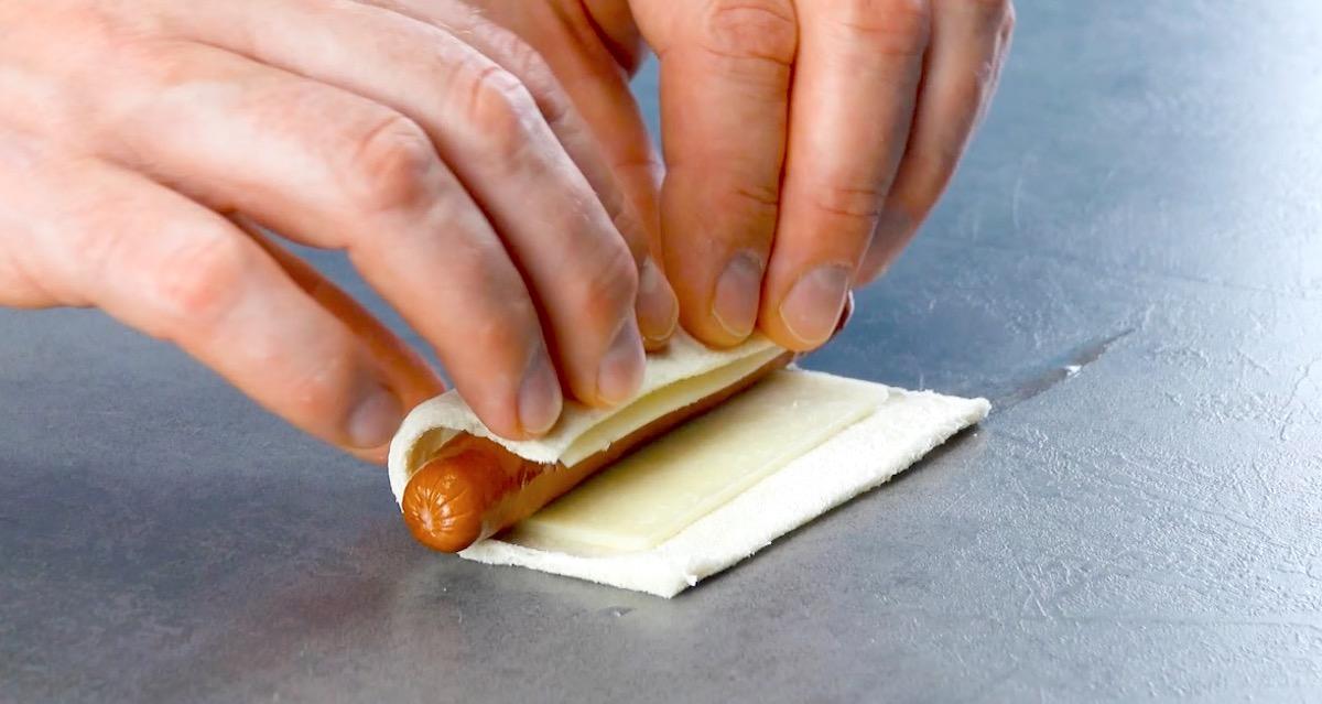 recheie o pão com queijo e salsicha
