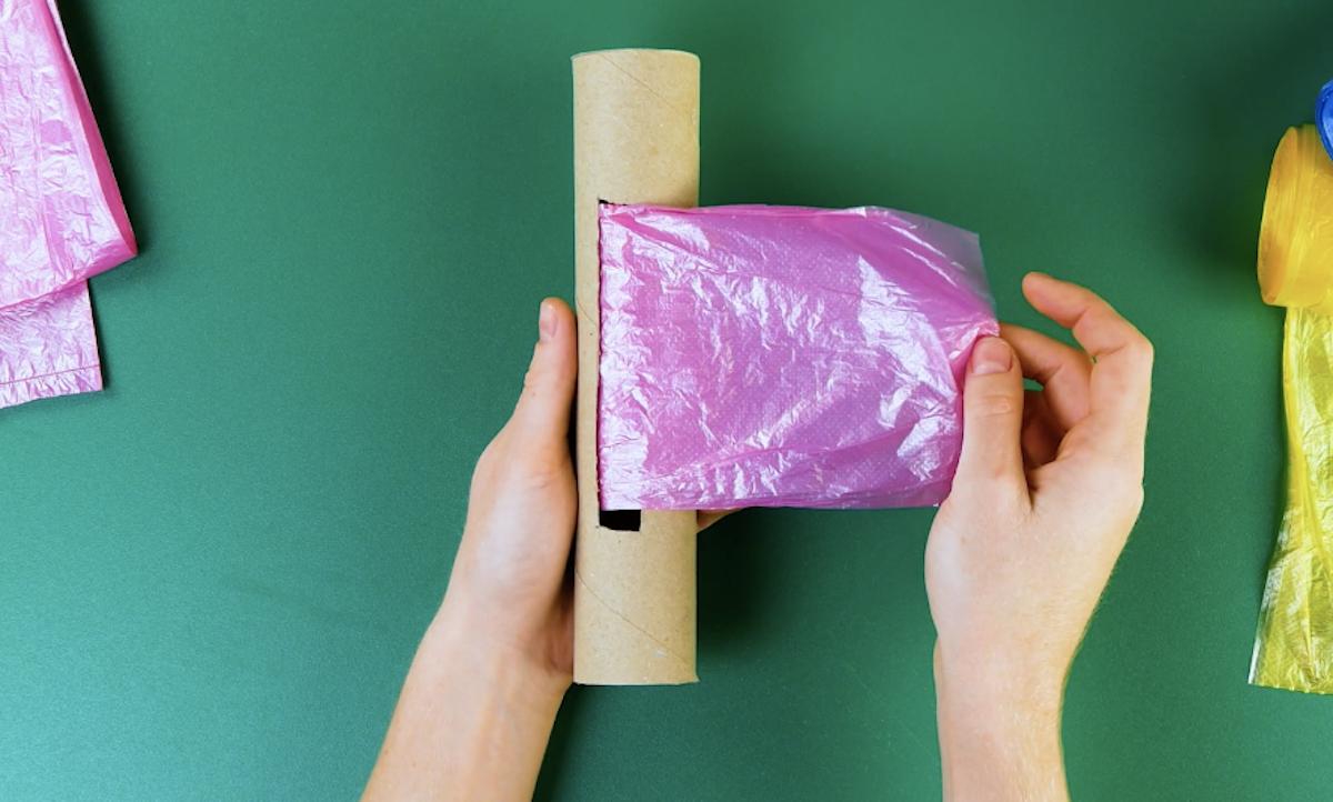 Insira o rolo de sacos de lixo no rolo de papel